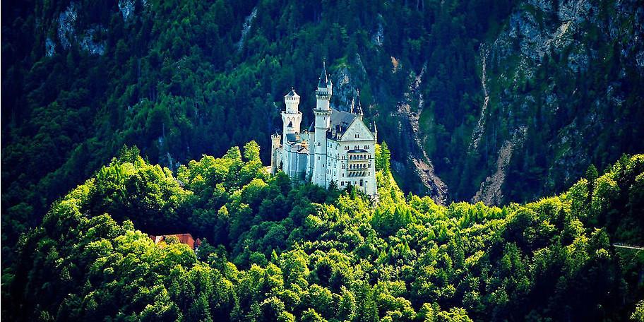 Es erwartet Sie der Blick auf das reale Schloss Neuschwanstein und die mystische Bergwelt der Umgebung